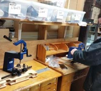 Clockmaker Bill Lea working with a bushing tool